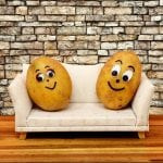 two potatoes with faces sitting on a beige couch with a brick background
