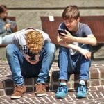 two young boys playing on their phones on a curbside.