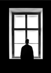 black and white image of man looking out a window